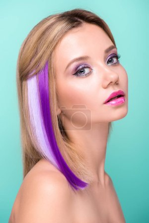 attractive young woman with bobbed hair with purple strands looking at camera isolated on blue