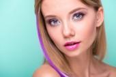 """Постер, картина, фотообои """"красивая молодая женщина с стриженый волос с пурпуровой нити, глядя на камеру, изолированные на синий"""""""