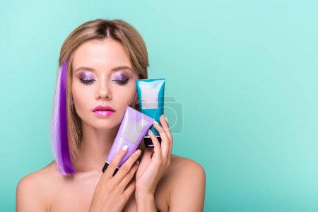 sensual young woman with colorful strands in hair holding coloring hair tonics isolated on blue