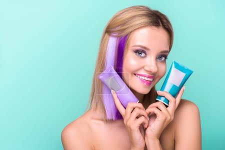 happy young woman with colorful strands in hair holding coloring hair tonics isolated on blue