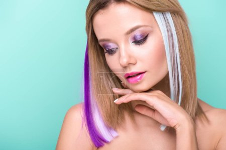 Photo for Close-up portrait of beautiful young woman with colorful strands in hair isolated on blue - Royalty Free Image