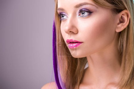 close-up portrait of beautiful young woman with colorful strands in hair looking away