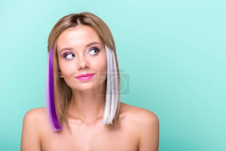 thoughtful woman with colorful strands in hair looking away isolated on blue
