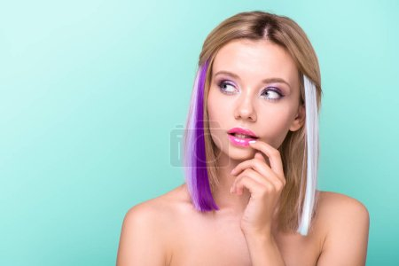 thoughtful young woman with colorful strands in hair looking away isolated on blue