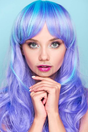 beautiful young woman with blue hair looking at camera isolated on blue