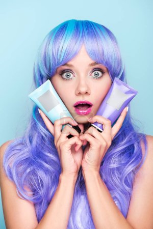 shocked young woman with tubes of coloring hair tonics isolated on blue