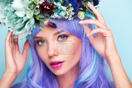 close-up portrait of young woman with curly blue hair and floral wreath isolated on blue