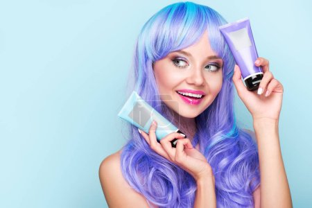 happy young woman with tubes of coloring hair tonics isolated on blue