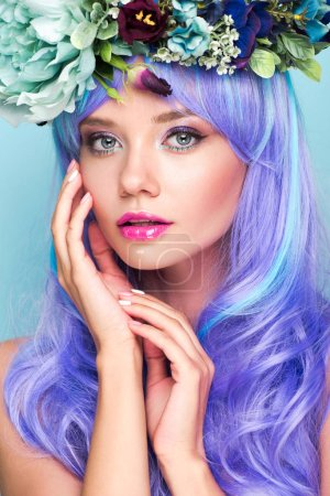 close-up portrait of attractive young woman with curly blue hair and floral wreath isolated on blue
