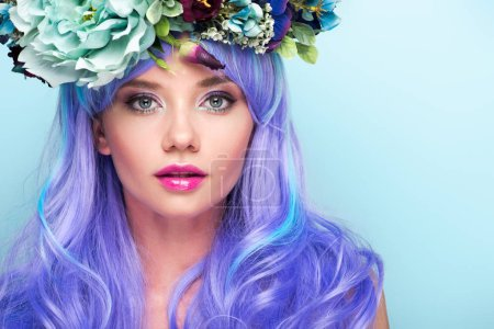 close-up portrait of beautiful young woman with curly blue hair and floral wreath isolated on blue