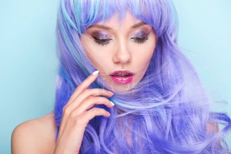 close-up portrait of beautiful young woman with curly blue hair isolated on blue