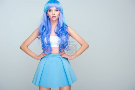 beautiful young woman with curly bright blue hair and arms akimbo isolated on grey
