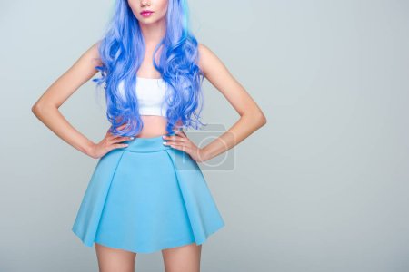 cropped shot of young woman with curly bright blue hair and arms akimbo isolated on grey
