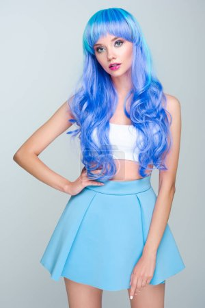 cropped shot of young woman with curly bright blue hair isolated on grey