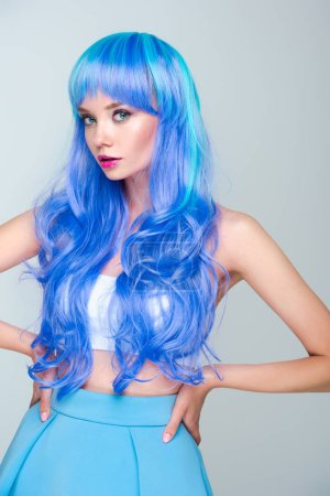 serious young woman with bright blue hair standing with arms akimbo and looking at camera isolated on grey