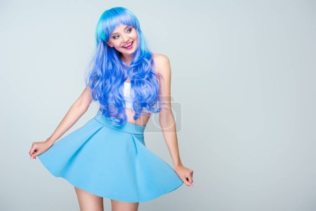 smiling young woman with bright blue hair and skirt isolated on grey