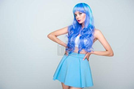 beautiful young woman with bright blue hair standing with arms akimbo and looking at camera isolated on grey