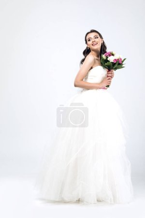 beautiful young bride in wedding dress with bouquet and looking away on white