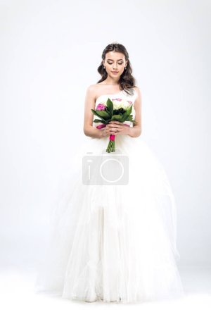 beautiful young bride in wedding dress with bouquet on white