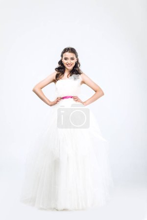 young bride in wedding dress with arms akimbo looking at camera on white