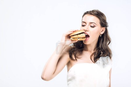 hungry young bride in wedding dress eating big burger isolated on white