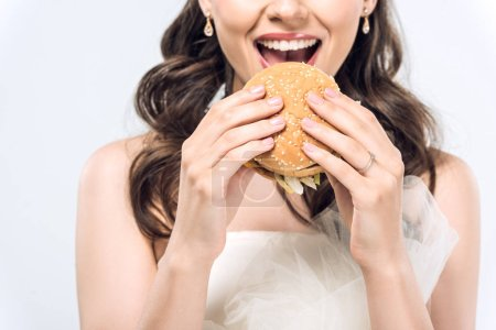 Photo for Cropped shot of hungry young bride in wedding dress eating hamburger isolated on white - Royalty Free Image