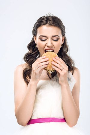 hungry young bride in wedding dress eating hamburger isolated on white