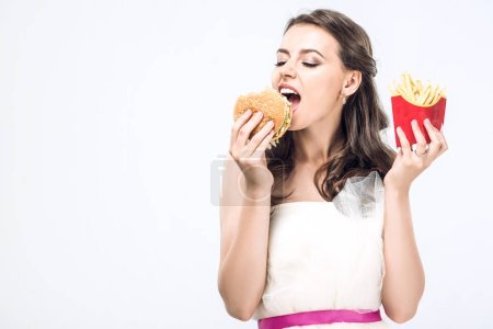 Photo for Hangry young bride in wedding dress eating burger and french fries isolated on white - Royalty Free Image