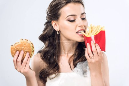young bride in wedding dress eating burger and french fries isolated on white