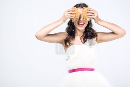 smiling young bride in wedding dress covering eyes with burgers isolated on white