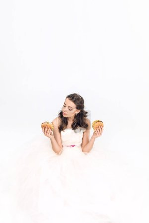 attractive young bride in wedding dress sitting on floor with burgers in hands on white