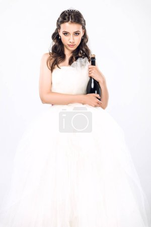 young bride in wedding dress holding bottle of champagne looking at camera isolated on white