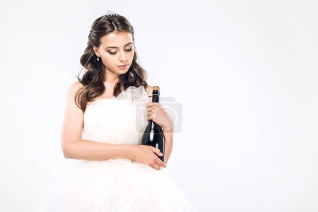 beautiful young bride in wedding dress holding bottle of champagne isolated on white