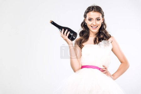 smiling young bride in wedding dress holding bottle of champagne isolated on white