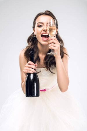 young bride in wedding dress with bottle and glass of champagne isolated on white