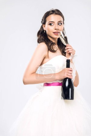 attractive young bride in wedding dress with bottle and glass of champagne isolated on white