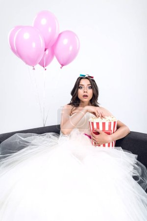 shocked young bride in wedding dress with bucket of popcorn watching movie isolated on white