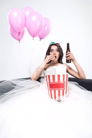 shocked young bride in wedding dress with beer and bucket of popcorn watching movie isolated on white