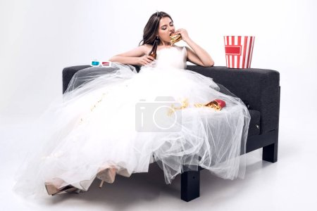 depressed hungry young bride in wedding dress sitting on couch and eating burger with beer on white