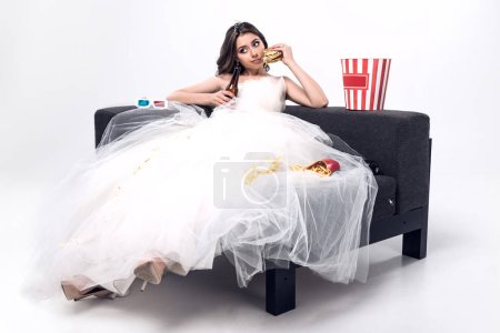 sad young bride in wedding dress sitting on couch with beer and junk food on white