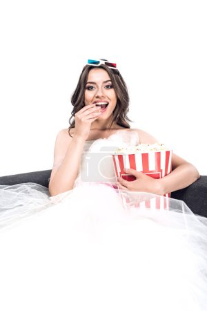 happy young bride in wedding dress and 3d goggles holding bucket of popcorn and watching cinema and sitting on couch isolated on white