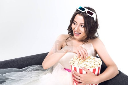 young bride in wedding dress and 3d goggles holding bucket of popcorn and sitting on couch isolated on white