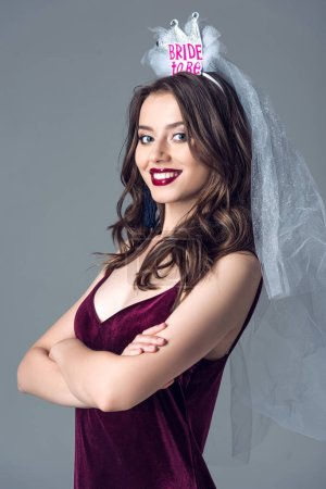 smiling future bride in veil for bachelorette party with crossed arms looking at camera isolated on grey