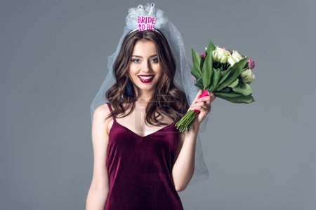 smiling future bride in veil for bachelorette party with bouquet looking at camera isolated on grey