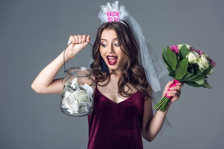 shocked future bride in veil for bachelorette party with flowers looking at jar of money isolated on grey