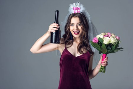 Photo for Smiling future bride in veil for bachelorette party with bouquet and champagne looking at camera isolated on grey - Royalty Free Image