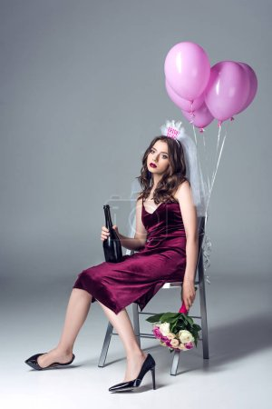 depressed future bride in veil for bachelorette party sitting on chair with champagne and flowers and looking at camera after party on grey