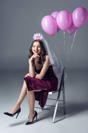 beautiful future bride in veil for bachelorette party sitting on chair with tied pink balloons on grey