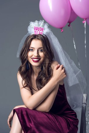 happy future bride in veil for bachelorette party sitting on chair with tied pink balloons isolated on grey