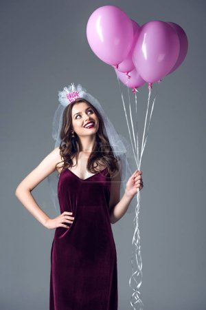 happy future bride in veil for bachelorette party holding bunch of pink air balloons isolated on grey